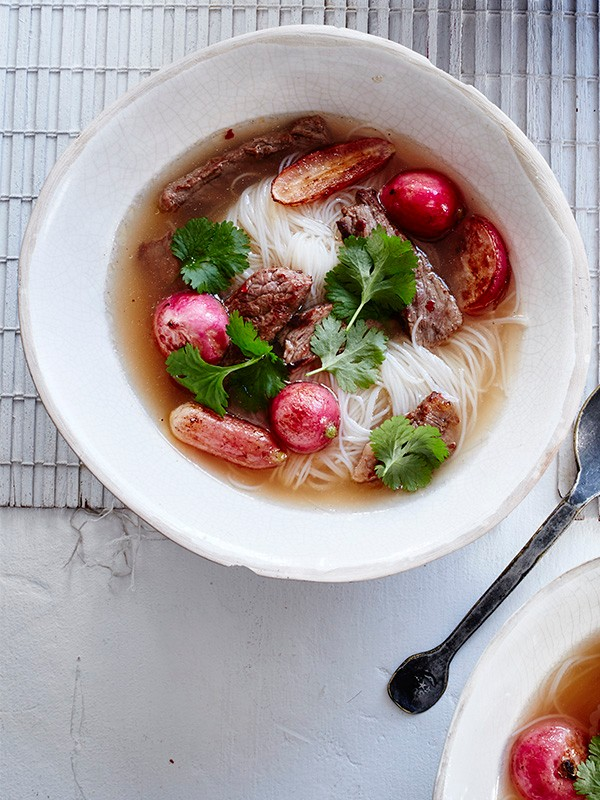 Beef Noodle Soup Recipe With Chilli and Radishes served in a deep white bowl on a marble surface