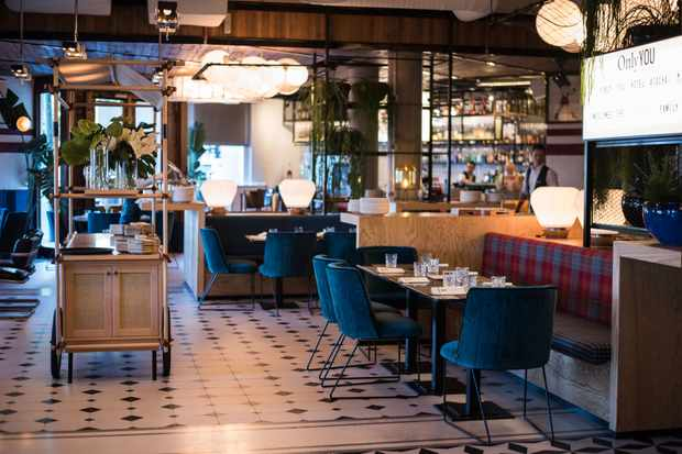 Interiors of Only YOU Hotel Atocha, Madrid. The bar area has black and white tiled floor, blue velvet chairs and a central bar
