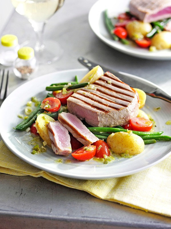 A white plate with lightly grilled tuna with Potato, tomato and green bean salad