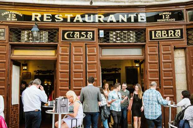 A bar in Madrid is has brown tiles on the outside and the word 'Restaurante' written in capital letters on the front. There are people stood and sat outside drinking