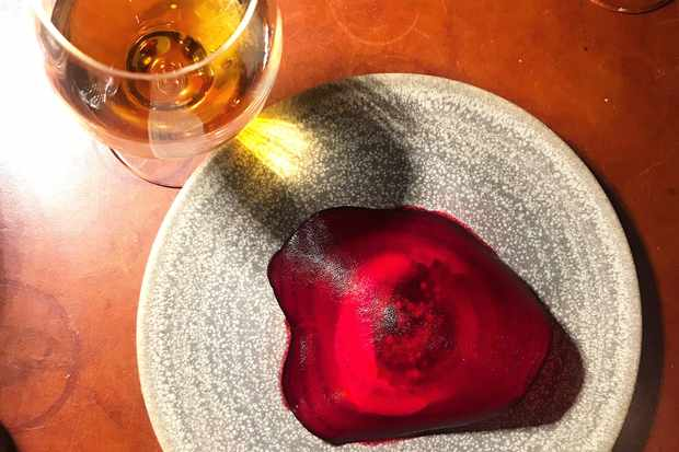 Glass of white wine and grey plate with a slice of beetroot on at Koka Gothenburg