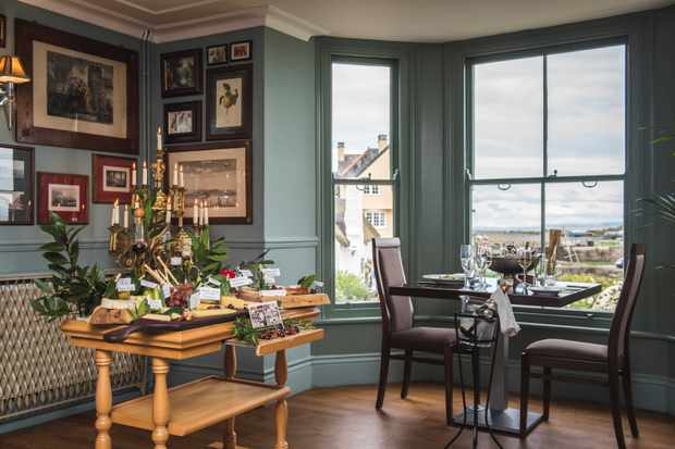 A dining room has duck egg blue walls and windows looking out over the sea. There is a table set in the bay window and pictures all over the wall