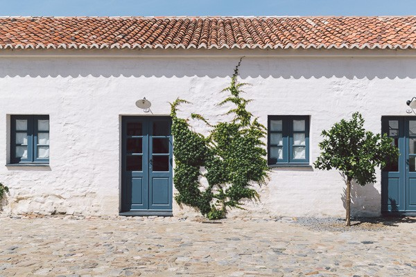 A white house in Portugal with blue doors, blue windows and greenery growing up the house
