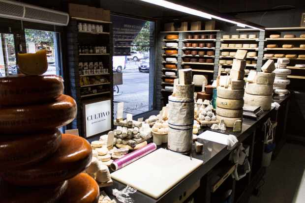 A Spanish cheese store with walls lined with shelves, all stocked with cheese. There is a cheese counter too with blocks of cheeses