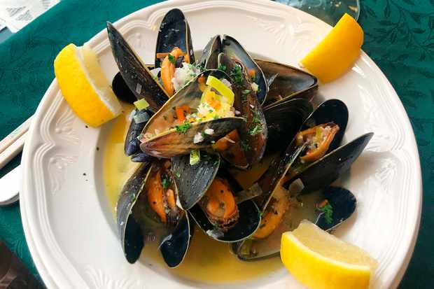 A plate of mussels on a dark green table cloth with a half filled pint of beer