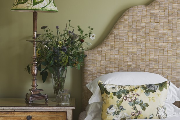 A pale green wall with a bed and side table against it. The table has flowers on