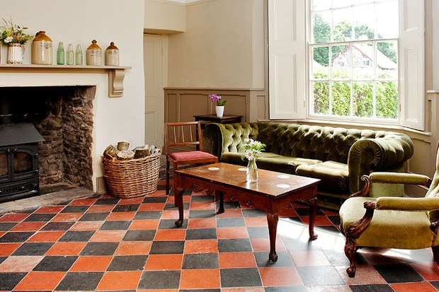 The sitting room at The Dolaucothi Arms, Carmarthenshire with a green chesterfield sofa, log burner, wall panelling, shuttered sash windows and a chequered floor