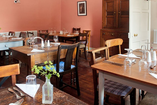 The dining room at The Dolaucothi Arms, Carmarthenshire with terracota-coloured walls, reupholstered chairs, original dark wooden floor and artwork on the walls