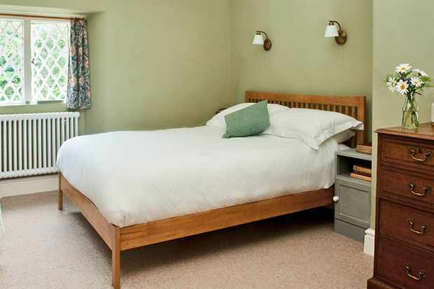 A simple room at The Dolaucothi Arms, Carmarthenshire with double bed, casement window and antique chest of drawers