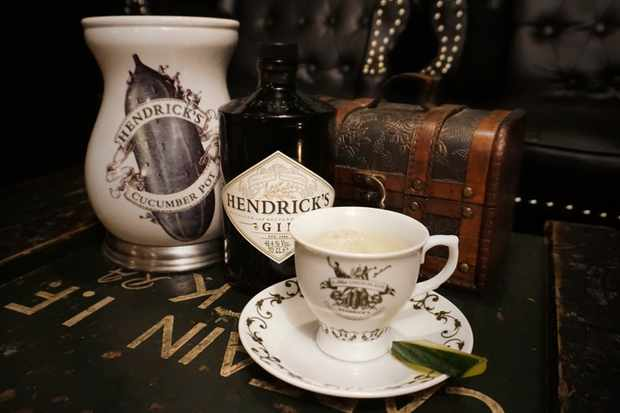 Hendricks gin bottle on a table with a Hendricks teacup with a chest in the background