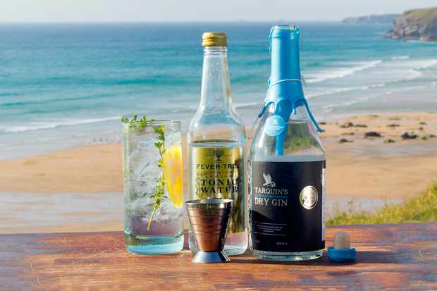 Tarquins gin bottle and a glass of gin and tonic on a beach with blue water in background