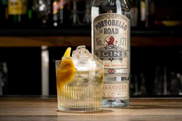 Portobello Road gin bottle on a table with a glass tumbler in front filled with gin and tonic, ice and a grapefruit peel
