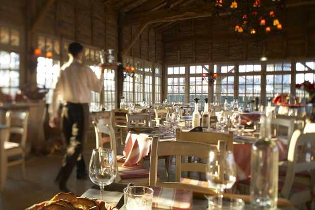 A waiter walking through a conservatory dining room at Les Sources de Caudalie