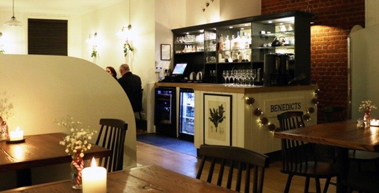 The dining room at Benedicts, Norwich with wooden floors and candlelit tables