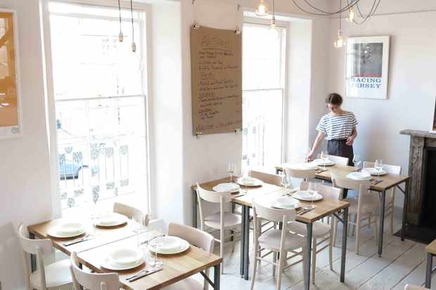 A waitress in a stripy top at Curator Kitchen Totnes laying one of three tables in a white dining room with white wooden floorboards