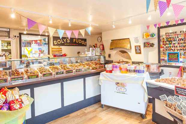 Roly's Fudge Shop Totnes a counter lined with 9 flavours of fudge and pastel coloured flags strung up above