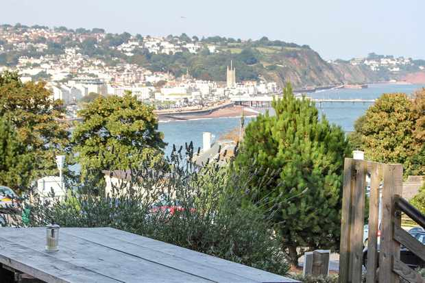 A terrace overlooking some hedges and an English seaside bay at Café ODE