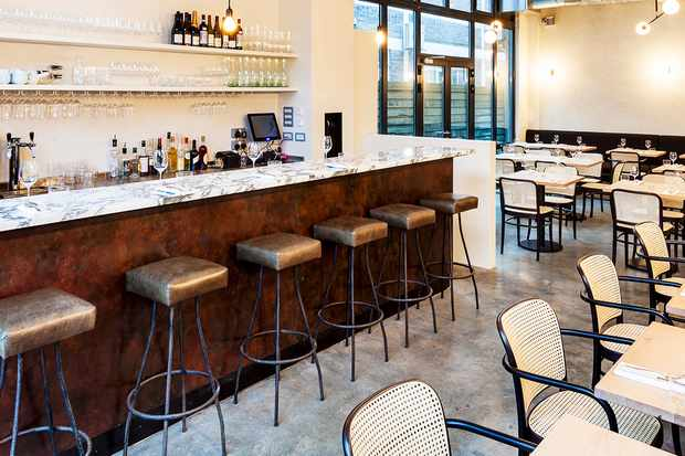 A sleek bar at Ellory, London with metallic bar stools, a marble countertop and modern light fittings