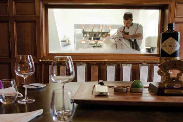 The chef's pass at Hampton Manor Hotel with a table and wine glasses in the foreground