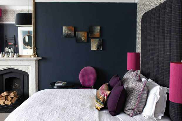 Hampton Manor Hotel bedroom with an open fireplace, a dark blue painted wall and a bed, with pink lampshades