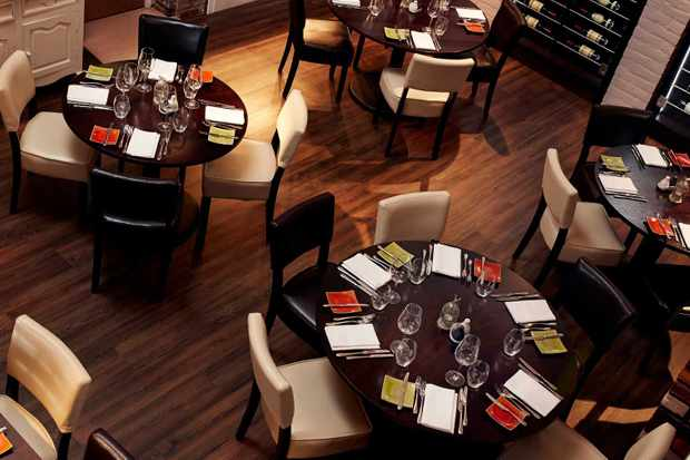 An aerial shot of the dining room at Peace & Loaf, Newcastle with dark brown wooden tables and matching chairs