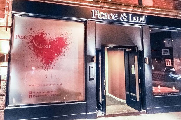 An exterior shot of Peace & Loaf in Newcastle with large windows and an illuminated shop sign