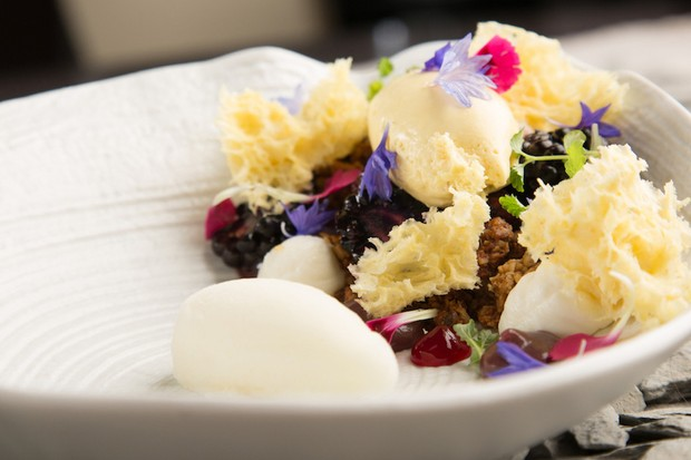 A close-up of an elegant dish at Peace & Loaf, Newcastle with edible flowers