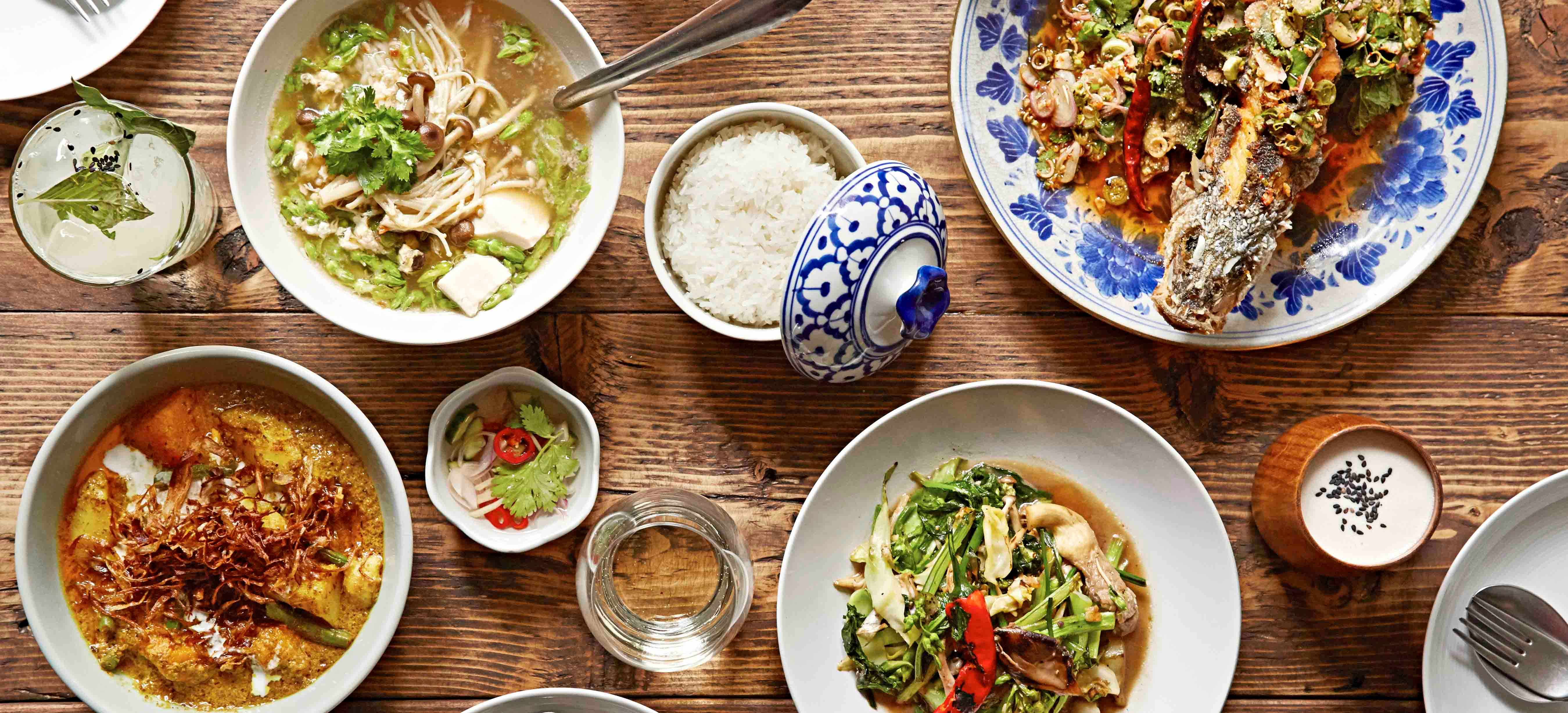 Overhead shot of Thai dishes on a wooden table at Somsaa