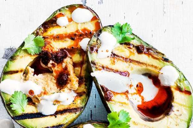 Grilled avocado halves with harissa hummus and tahini yogurt