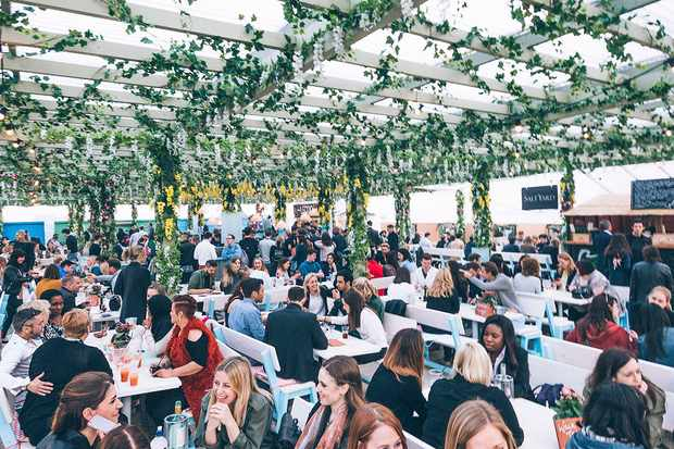 A wide shot of Pergola on the Roof bar in London with busy tables and foliage hanging from the ceiling