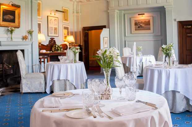 An elegant, blue carpeted dining room at Llangoed Hall, Brecon, Wales with high ceilings, plenty of natural light, white tablecloths and oil paintings on the wall