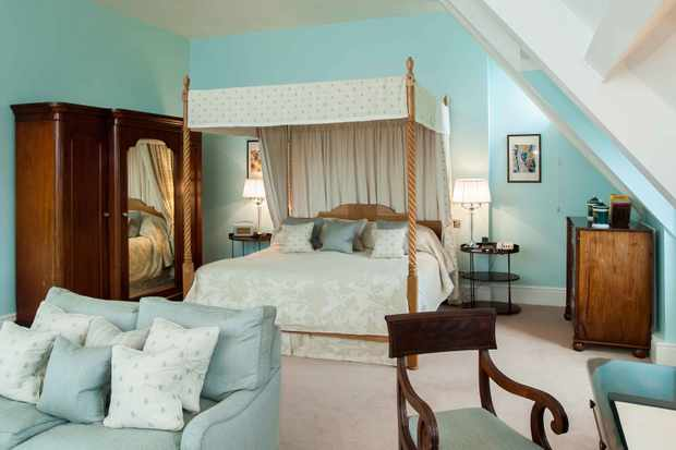 A large bedroom at Llangoed Hall, Brecon with powder blue walls and matching sofas, a grand four-poster bed and mahogany furniture