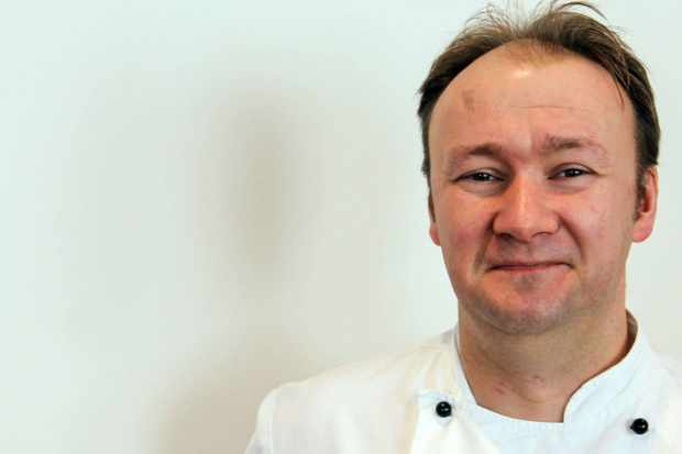 A smiling male chef dressed in chef's whites posing for the camera