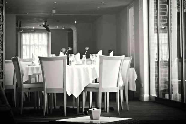 A black-and-white shot of the dining room at The Ostlers, Horndon-on-the-Hill with white tablecloths and floor-to-ceiling windows