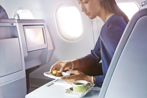 finnair-business-woman-having-a-dessert on a plane