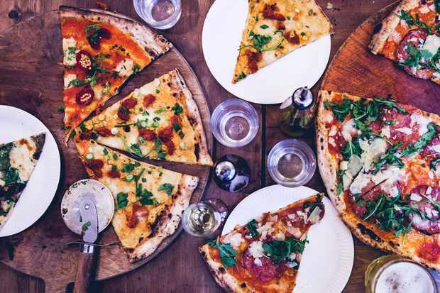 A selection of pizzas and pizza slices on white plates and wooden boards