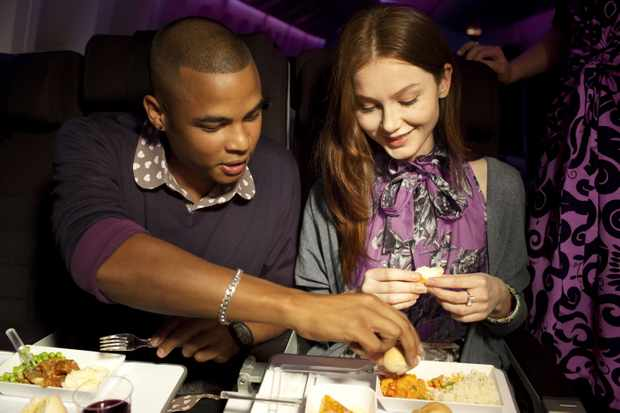 man and woman eating airline food