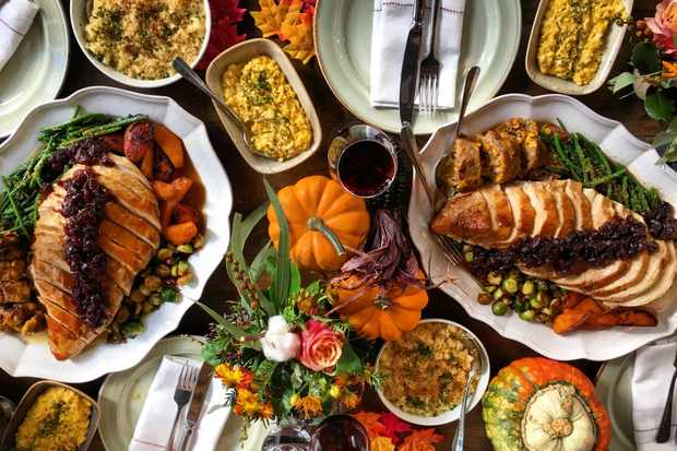 Thanksgiving feast at Rail House Cafe. On the table there is plates of sliced turkey, pumpkins, mac and cheese, stuffings and lots of vegetables. There are a few plates with knives and forks on too