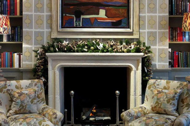 A cosy fire with armchairs next to it at The Ham Yard Hotel. There is a painting above the fireplace and holly is surrounding the fireplace
