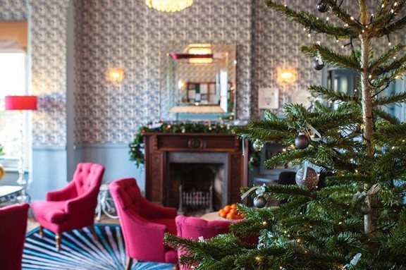 A large sitting room with red chairs and a Christmas tree at A cosy fire with armchairs next to it at Titchwell Manor. Their is a fireplace in the background with a mirror hanging above it, with the Christmas tree in the foreground