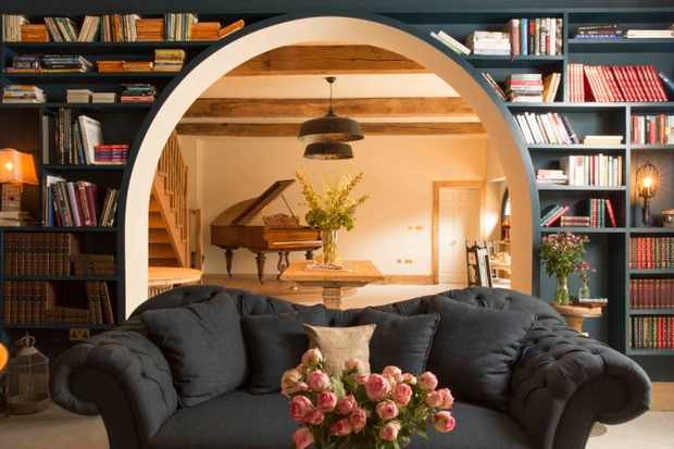 big black sofa infront of an archway with book shelves on the walls and a grand piano in the background