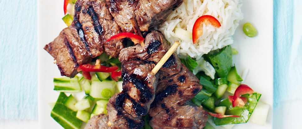 Teriyaki steak skewers with chopped green Asian salad