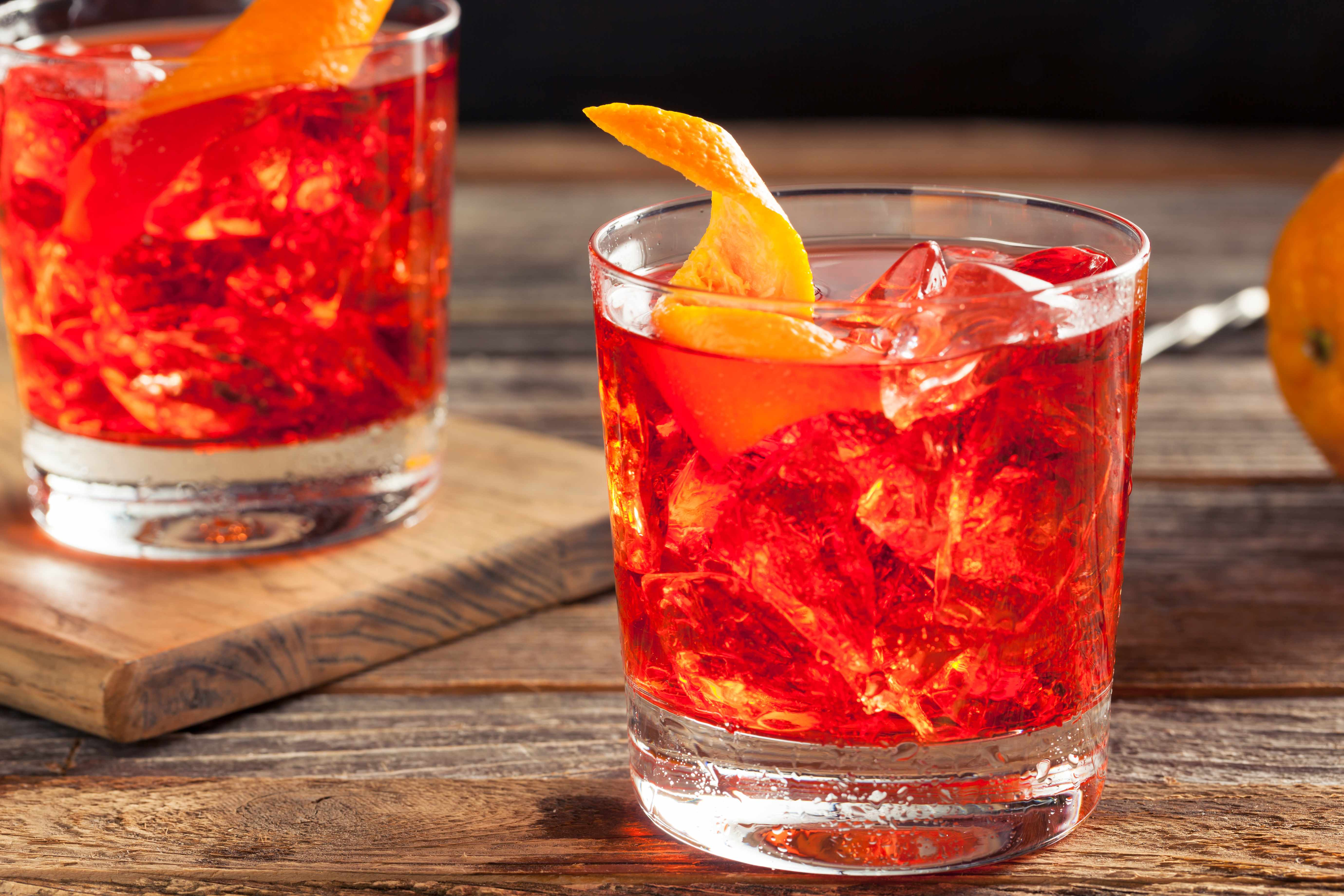 Negroni Cocktail Recipe - Negroni sbagliato: bright red cocktail served in a glass tumbler with an orange twist