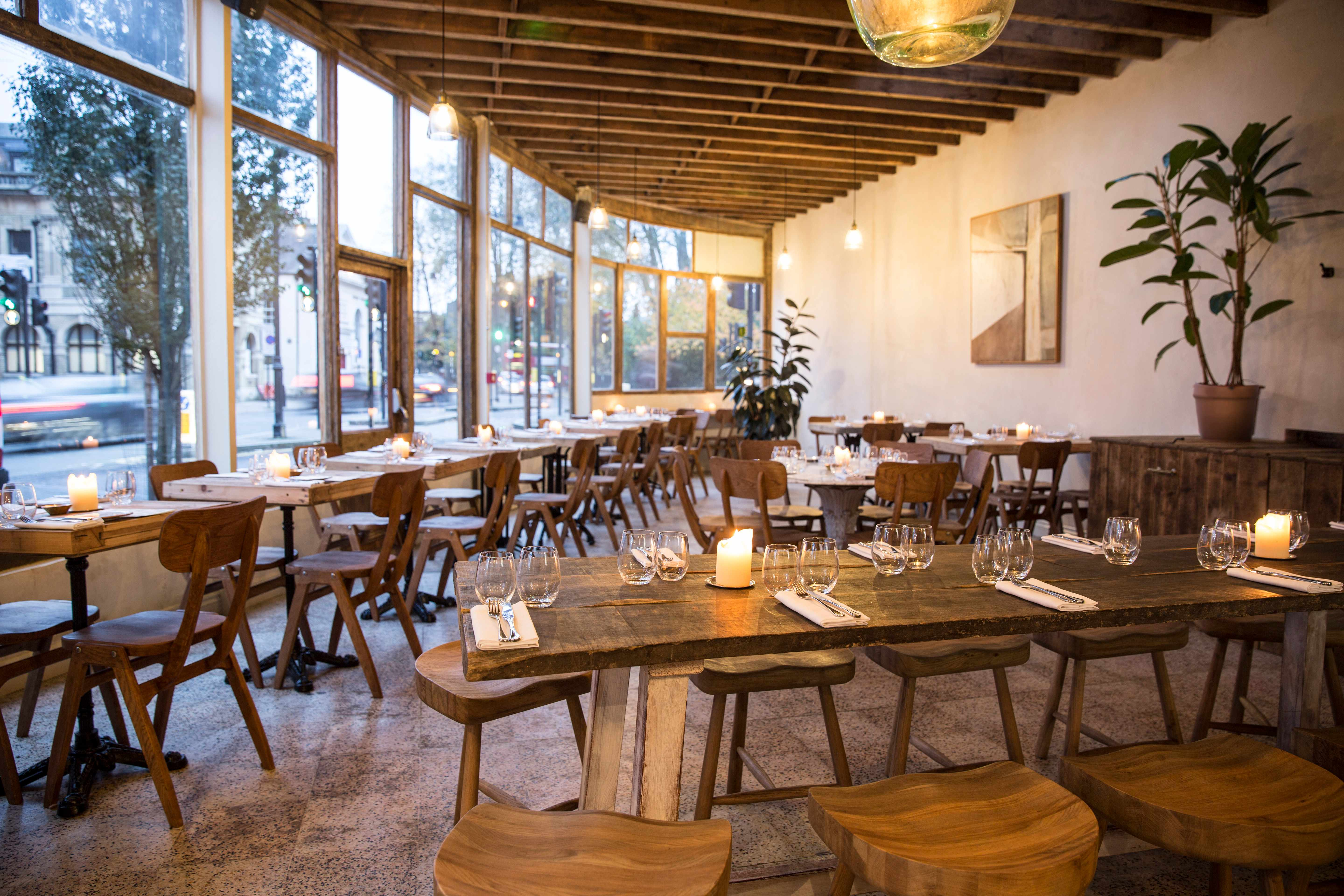 Exposed wooden rafters, wooden floors and matching tables. Bright and breeze, big glass winds with natural light streaming in