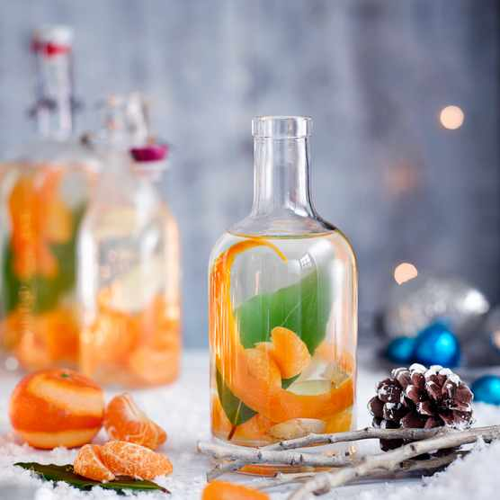 Christmas Gin Recipe With Clementine, Ginger And Bay on a snow covered table with pine cones and clementine segments