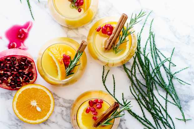 Orange Fizz Mocktail Recipe with Rosemary - non-alcoholic cocktail served with cinnamon sticks, orange slices, rosemary and pomegranate seeds