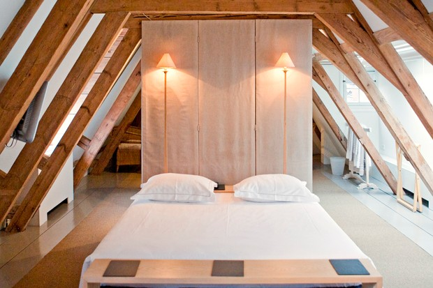 A bed under eaves in a loft room at The Dylan hotel in Amsterdam