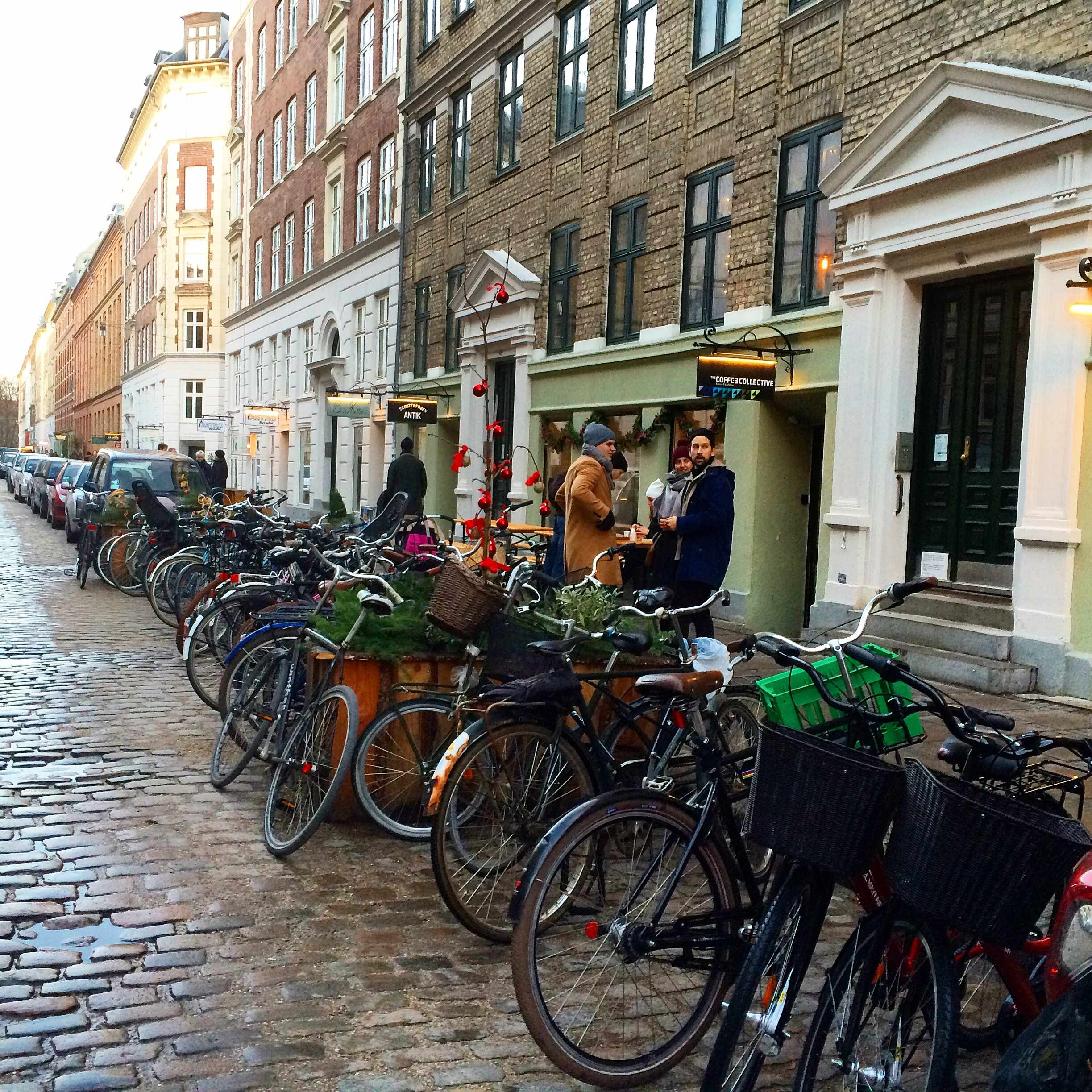 Lots of bikes lined up outside a coffee shop and people drinking coffee