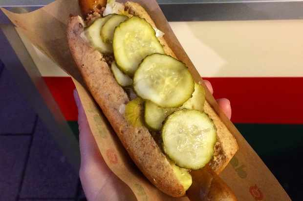 A hand holding a hot dog topped with pickled gherkins