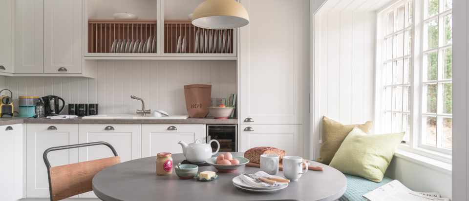 round kitchen table in a light and bright kitchen by a window with a window seat